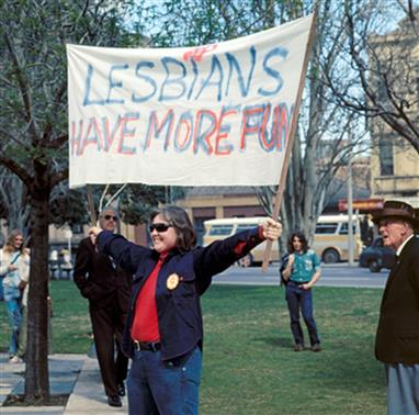 Woman in park holding banner reading Lesbians Have More Fun